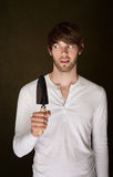 Sneaky Man Holding Trowel. Sneaky handsome Caucasian man with a garden trowel Stock Photo