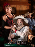 Sneaky Old Gambler. Sneaky old poker player gets winning card from showgirl in saloon Stock Photos