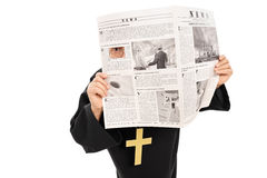 Sneaky priest peeking through a hole in newspaper. Isolated on white background Royalty Free Stock Photos