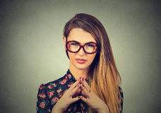 Sneaky, sly, scheming young woman in glasses plotting something Royalty Free Stock Images