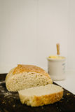 Sneaky Sourdough, homemade, on a breadboard with butter pot Royalty Free Stock Photos