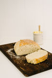 Sneaky Sourdough, homemade, on a breadboard with butter pot Royalty Free Stock Image