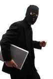 Sneaky Thief. A sneaky thief wearing a black suit is walking with a laptop, isolated against a white background Stock Images