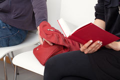 Sneaky thief. A sneaky thief trying to steal a bag of a woman sitting next to him Royalty Free Stock Image