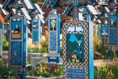 Sned och målade träkors i den glade kyrkogården i Sapanta, Rumänien Det är kyrkogården FN arkivfoton