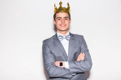 Sneering young handsome man wearing suit and crown keeping arms crossed Royalty Free Stock Image