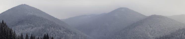 Sneeuw afgedekte bergketen onder gelaagde hemel Stock Foto's