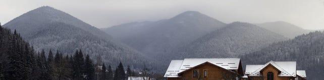 Sneeuw afgedekte bergketen onder gelaagde hemel Stock Afbeelding