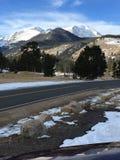 Sneeuw afgedekte bergpieken en weg stock foto