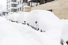 Sneeuw behandelde auto's en ijzige straat in Sofia, Bulgarije Stock Foto's