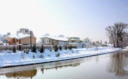 Sneeuw behandelde huizen door een rivier Stock Afbeelding