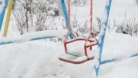 Sneeuw behandelde schommeling bij een speelplaats in de winter stock video