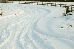 Sneeuw behandelde weg met bandsporen Royalty-vrije Stock Afbeeldingen