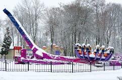 Sneeuw-bekroonde aantrekkelijkheidsdierenriem in de winterpark tijdens sneeuwval Stock Afbeeldingen