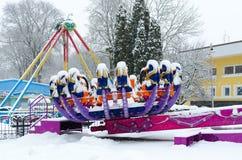 Sneeuw-bekroonde aantrekkelijkheidsdierenriem in de winterpark tijdens sneeuwval Royalty-vrije Stock Foto's