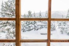 Sneeuw bosbomen in de sneeuw buiten het venster met houten Royalty-vrije Stock Afbeelding