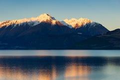 Sneeuw-Caped bergen en meer op zonsondergang Het landschap van de aard stock foto