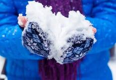 Sneeuw in de handen van een jong meisje Het kind dient vuisthandschoenen met verse sneeuw in royalty-vrije stock afbeeldingen