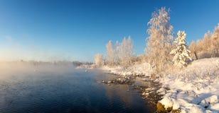 Sneeuw de winterbos met struiken en bomen op de banken van de rivier met mist, Rusland, het Oeralgebergte royalty-vrije stock afbeeldingen