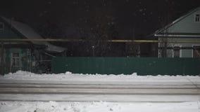 Sneeuw die met straatlantaarnstralen bij nacht vallen De dalings van de lijn bekwame sneeuw video als achtergrond stock video