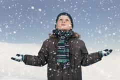 Sneeuw die neer bij jongen omhoog het kijken valt Royalty-vrije Stock Foto's