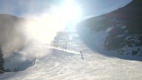 Sneeuw die op helling maken Skiër dichtbij een sneeuwkanon die verse poedersneeuw maken De toevlucht van de bergski in de winterr stock videobeelden