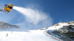 Sneeuw die op helling maken Skiër dichtbij een sneeuwkanon die verse poedersneeuw maken De toevlucht van de bergski in de winterr stock video