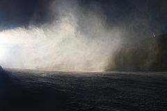 Sneeuw die op helling maken Skiër dichtbij een sneeuwkanon die verse poedersneeuw maken De toevlucht van de bergski in de winterr royalty-vrije stock fotografie