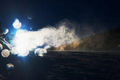 Sneeuw die op helling maken Skiër dichtbij een sneeuwkanon die verse poedersneeuw maken De toevlucht van de bergski in de winterr stock foto's