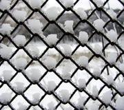 Sneeuw en ijs op een metaalnet stock fotografie