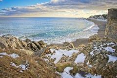 Sneeuw en rotsachtig overzie van de oceaan en het strand tijdens de winter stock afbeeldingen