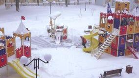 Sneeuw het schoonmaken in de speelplaats stock videobeelden