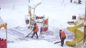 Sneeuw het schoonmaken in de speelplaats stock video