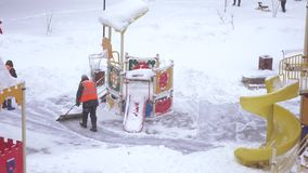 Sneeuw het schoonmaken in de speelplaats stock footage