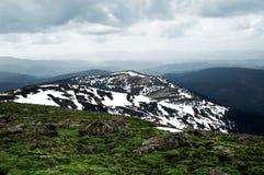 Sneeuw heuvel die van grasrijke berg wordt gezien Stock Afbeeldingen