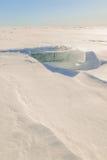 Sneeuw, ijs, heuveltjes op snow-covered ijs van meer. Royalty-vrije Stock Afbeeldingen