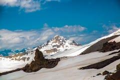 Sneeuw op de bergen tegen de blauwe hemel in de wolken Het Elbrus-gebied De Kaukasus royalty-vrije stock foto