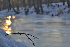 Sneeuw op het detail en de zonbezinningen van de rivierbank over bevroren rivier Royalty-vrije Stock Afbeeldingen