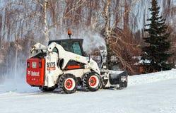 Sneeuw schoonmakende bestratingen en straten van stad die binnen behandeld zijn Stock Afbeelding