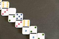 Sneeuwbaleffectschot Kijk neer voor dominospel op zwarte achtergrond Domino's die op een rij vooraan vallen Domino'sspel Stock Foto's