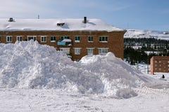 Sneeuwbank dichtbij het high-rise gebouw in het dorp stock afbeelding