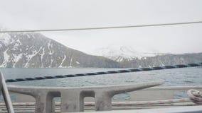 Sneeuwberg en klippenlandschap van varend schip op blauwe overzeese golven stock footage
