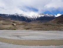 Sneeuwberg met donker weer bij afstand en de modderrivier in woestijn Royalty-vrije Stock Afbeelding