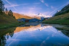 Sneeuwbergen en Houten Chalet die in Hoogtemeer bij S nadenken stock foto