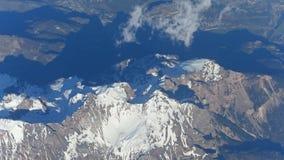 Sneeuwbergpieken, wolken en verre alpiene steden in een vallei stock videobeelden