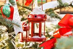 Sneeuwboom met rode kandelaar, speelgoed en banden wordt verfraaid die stock fotografie