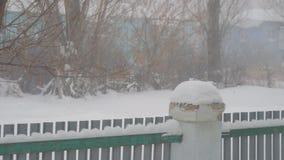 Sneeuwdalingen op de achtergrond van kleine omheining stock videobeelden