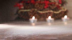 Sneeuwdalingen op een houten lijst met het branden van kaarsen Kerstmis en Nieuwjaarsamenstelling stock video