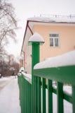 Sneeuwdia op de groene omheining op de huisachtergrond Royalty-vrije Stock Foto