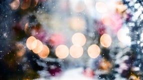 Sneeuwend Abstract patroon met het sneeuwen tegen de winterbos en bokeh het bos van de lichtenwinter en bokeh lichten Royalty-vrije Stock Foto's